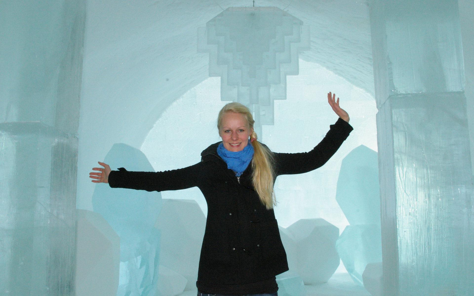 Birte steht im Eishotel Jukkasjärvi in Schweden. Im Hintergrund sieht man einen Kronleuchter aus Eis.