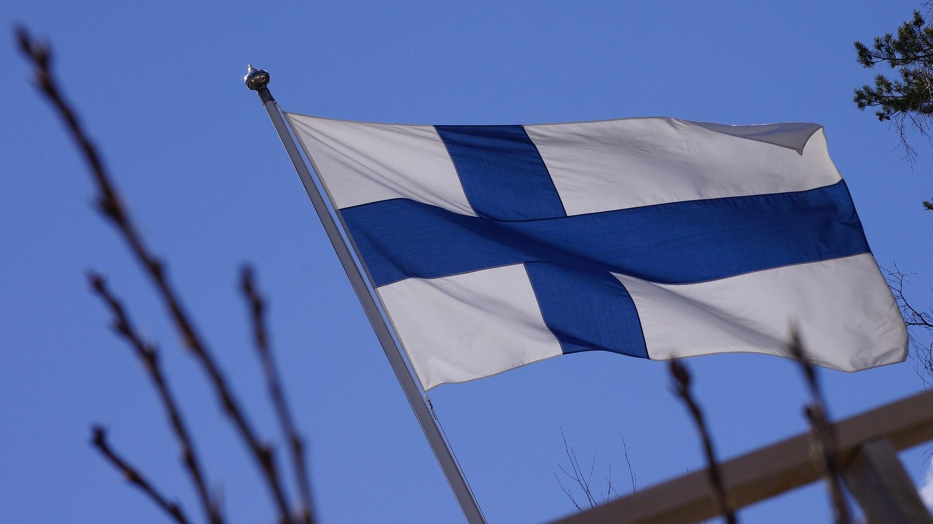 Die Finnische Flagge vor blauem Himmel.