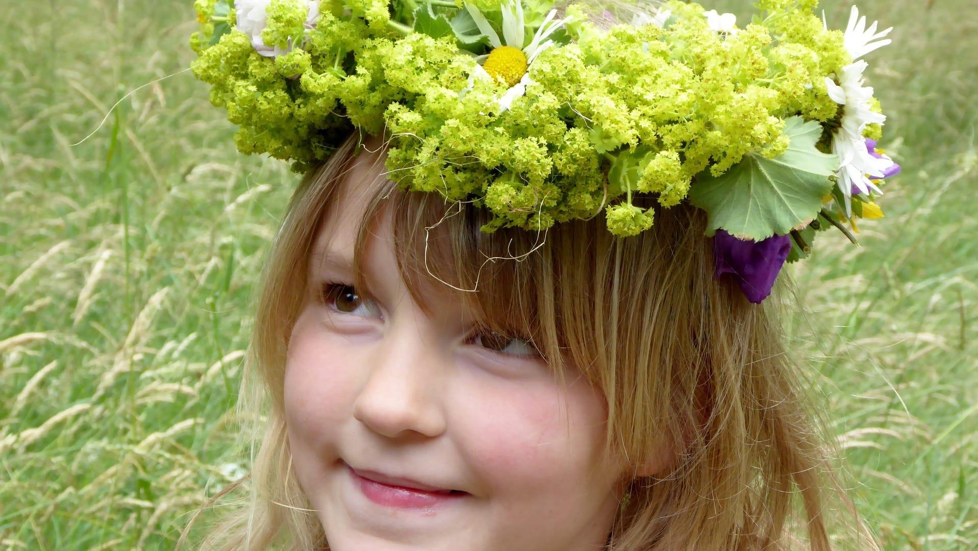Unverheiratete Frauen tragen an Mittsommer einen Blumenkranz und träumen von ihrem Zukünftigen.