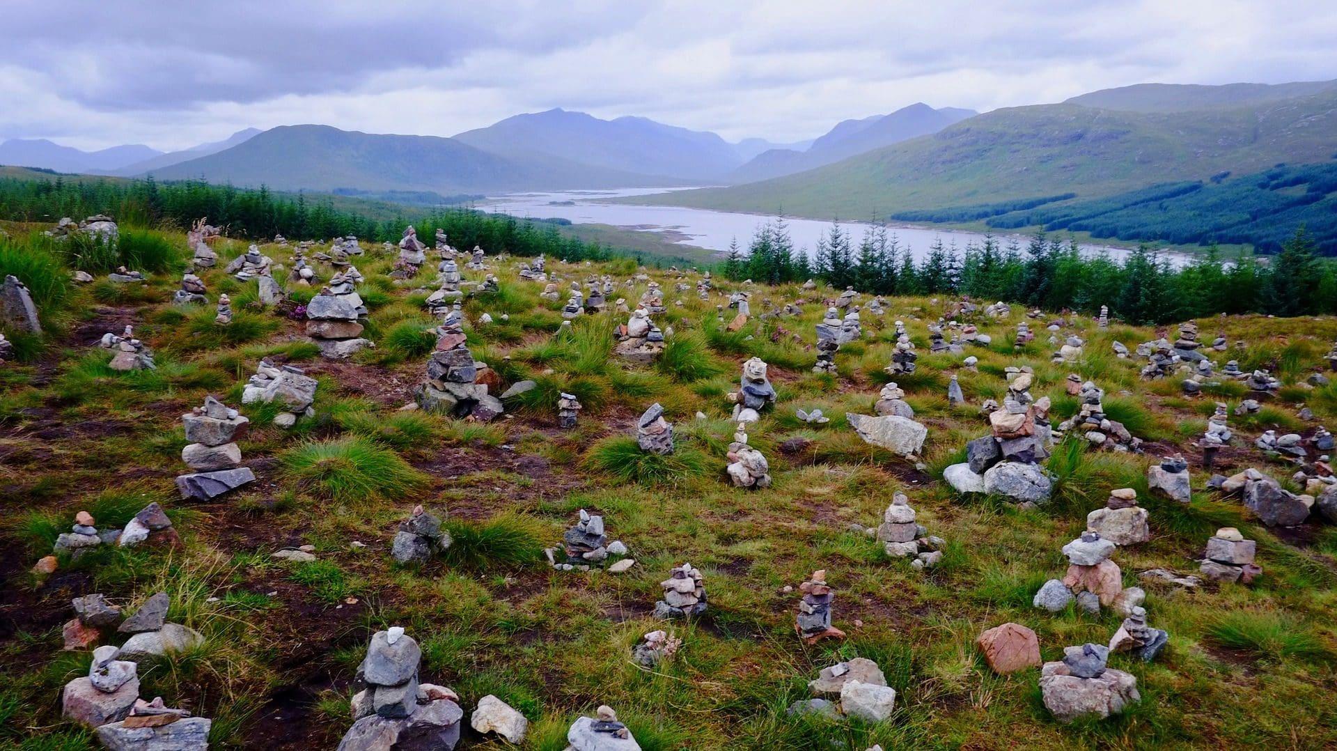 Viele Steinmännchen auf grüner Wiese vor Bergkulisse