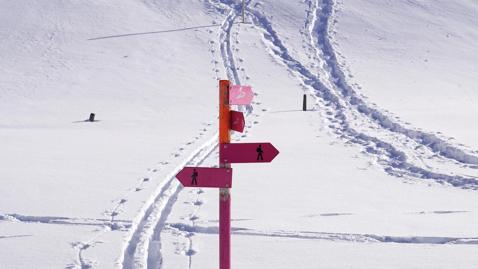 Ein roter Wegweiser steht im Schnee, dahinter sind Fußspuren zu erkennen.